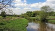 English countryside, trees reflected in the waters of a river, blue skies with fluffy white clouds above
