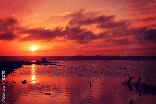 Poster Bordeaux Beautiful sunny red colorful sunset on the lake with stones, wooden posts and reflection, natural seasonal summer vacation background