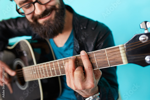 Fotografering  Bearded hipster man hand playing on acoustic guitar.