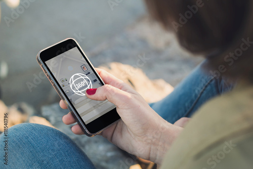 Woman looking at her smartphone with 360 degree view Fototapeta
