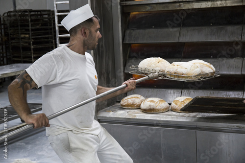 Baker taking out freshly baked bread from the oven of a bakery