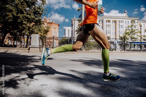 Zdjęcie XXL nogi młodego sportowca w skarpetkach kompresji działa maraton