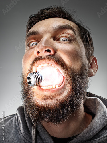 Photo Caucasian man with bulb in his mouth on gray background