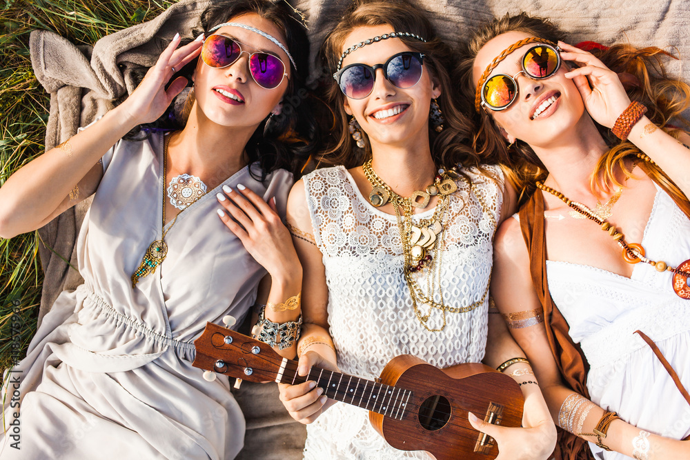 Fototapeta Three cute hippie girl lying on the plaid outdoors, best friends having fun and laughing, play ukulele, sunglasses, feathers in their hair, bracelets, flash tattoo, indie, Bohemia, boho style top view