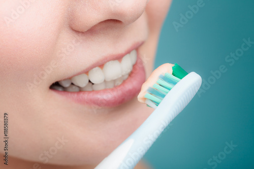 Fotografie, Obraz  woman holds toothbrush with toothpaste cleaning teeth