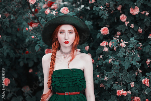 Photo  Red-haired girl with blue eyes and pale skin in a green hat and dress with a red belt