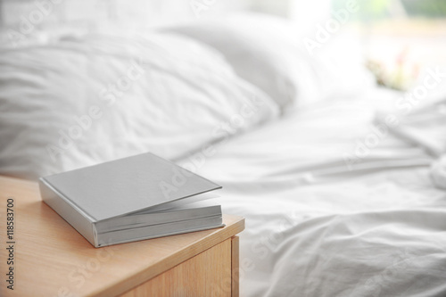 Closed book on wooden bedside table near crumpled bed Wallpaper Mural