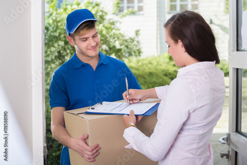 Fotografía  Woman Signing Receipt Of Delivery Package