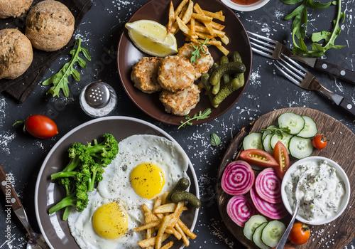 Fotografía  Vector del almuerzo - huevos fritos, bolas de pescado, papas fritas, verduras, salsas, pan hecho en casa sobre un fondo oscuro