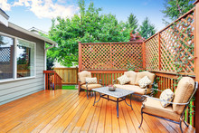 Spacious Wooden Deck With Patio Area And Attached Pergola.