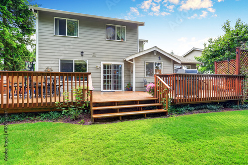 Obraz Back yard house exterior with spacious wooden deck - fototapety do salonu