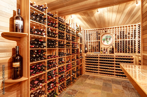Bright home wine cellar with wooden storage units with bottles. Canvas Print