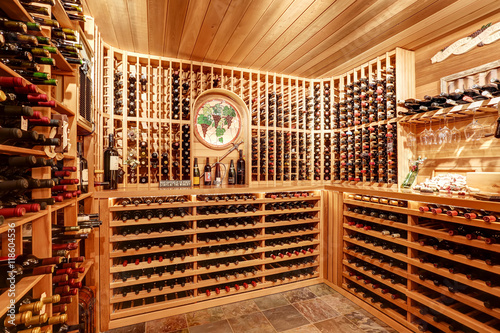 Photo Bright home wine cellar with wooden storage units with bottles.