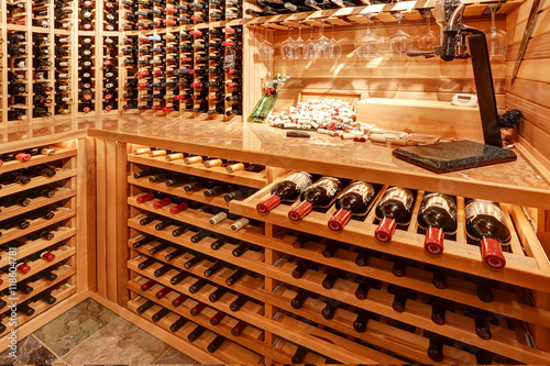 Bright home wine cellar with wooden storage units with bottles. Wallpaper Mural