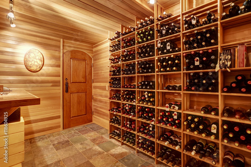 Fotografia  Bright home wine cellar with wooden storage units with bottles.