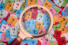 Pile Of Question Marks And Magnifying Glass