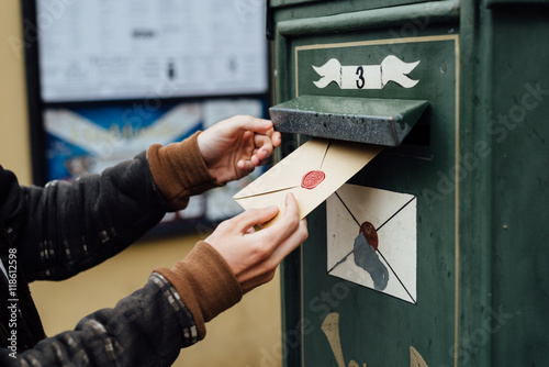 Fotografie, Obraz Posting letter to old postbox on street