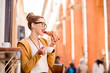 Young woman having italian breakfast with croissant and coffee at the cafe on the street in Bologna city. Soft focus with small depth of field