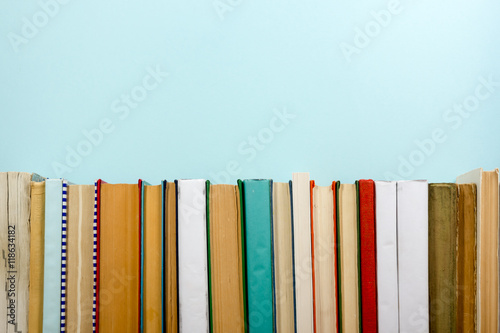 Fotografija  Books on grunge wooden table desk shelf in library