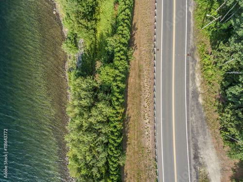 widok-z-lotu-ptaka-odludnej-czesci-drogi-autostradowej-wzdluz-linii-drzew-i-brzegu-jeziora