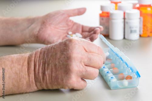 Stampa su Tela Elderly man sorting daily medication into a pill box.