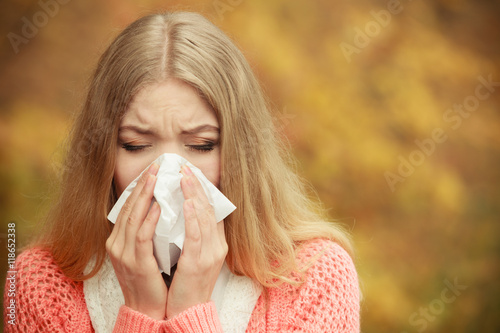 Fotografia  Sick ill woman in autumn park sneezing in tissue.