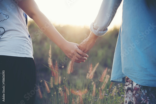 Poster Natuur A young couple holding hands. In Nature sunrise