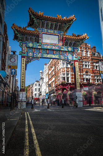 The Gate in chinatown, london, England with glazed yellow tiles, a golden dragon, painted panels, two white jade plaques and gold foil. The Chinese text translates 'Peace and Prosperity to Chinatown'