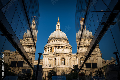 Poster Smal steegje St Paul's cathedral seen from a narrow alley enclosed by glass buildings and reflecting in the shiny surface at morning dawn