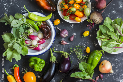 Photo Fresh vegetables - radishes, eggplant, pepper, tomatoes, onion, garlic on a dark wooden background