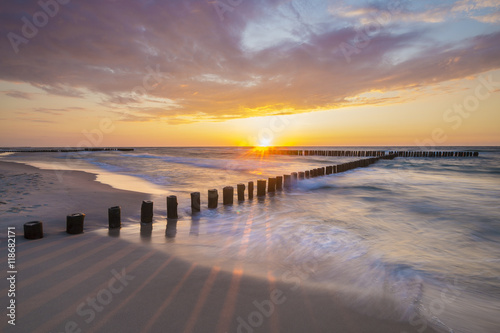 Garden Poster Light pink Sea landscape at sunset, sandy beach and cliff,waves breaking on the shore