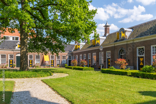 Fototapeta Green courtyard surrounded by old almshouses in Hofje van Staats in city of Haar