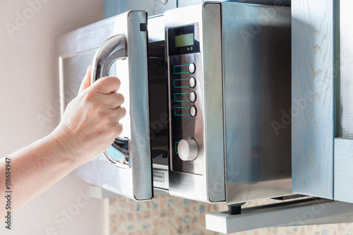 hand opens microwave oven for heating food