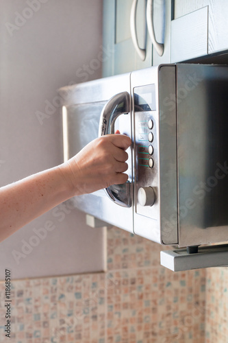 hand closes microwave oven for heating food