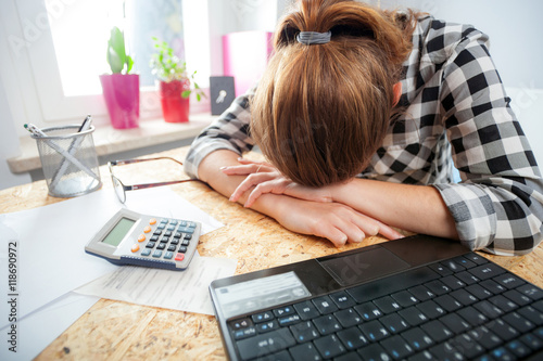Obraz na plátne  Stressed and depressed woman in home office calculating bills