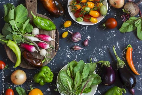 Assortment of fresh vegetables - tomatoes, radishes, eggplant, beets, peppers, garlic, onion, spinach. On a dark background, top view