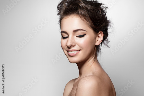 Plakat Beautiful woman with black arrows on eyes, clean skin and white teeth on grey ba