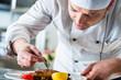 Koch oder Küchenchef beim Essen anrichten in Restaurant Küche