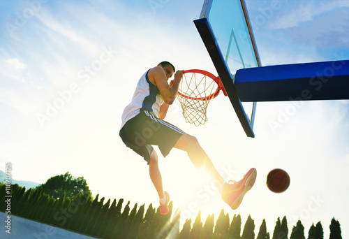 Photo  Street basketball player performing power slum dunk.