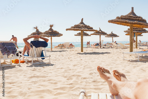 Spoed Foto op Canvas Tunesië Beach wooden straw sunshade umbrella legs people sunbathing relax Tunisia