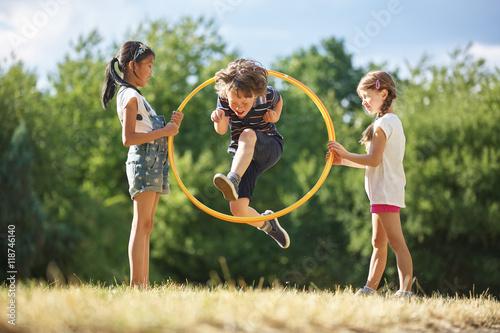 фотография  Junge springt durch Hula Hoop Reifen