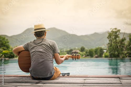 young man sitting on the pool at sunset with playing the guitar Canvas Print