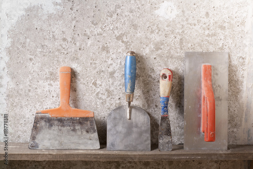 Construction tools on concrete background. Copy space for text. Set of assorted plaster trowel and spatula