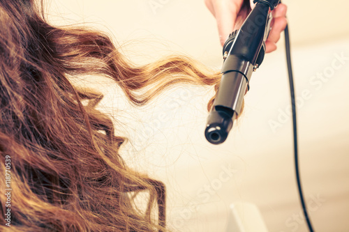 Fotomural Stylist curling hair for young woman.