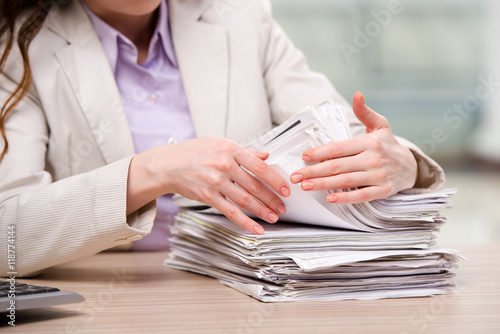 Fotografía  Businesswoman working with stack of papers