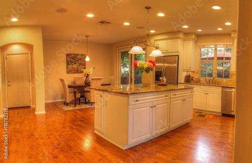 Irvine, CA, USA – August 19, 2016: Large kitchen with recessed lighting, wood floors, chrome stove, marble counter and feng shui decor Fototapeta