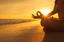 Yoga Concept. Hand Woman Practicing Lotus Pose On The Beach At Sunset.