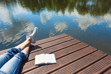 Relaxing And Vacation And Reading Concept. Woman Relaxing By The Waters Edge With A Book By Her Side.
