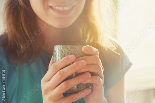 Photo sur Toile The girl drinking cup of coffee or tea in morning sunlight