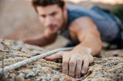 Man reaching for a grip while he rock climbs Wallpaper Mural